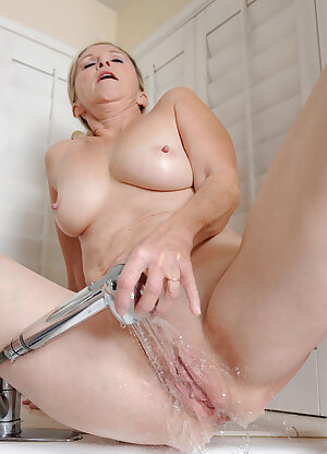 Older housewife Annabelle Brady washing her mature pussy in the kitchen sink