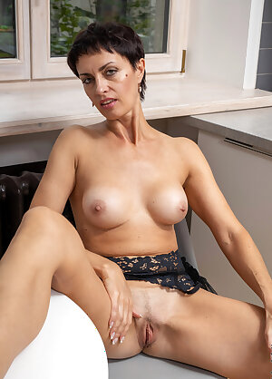 Short haired lady strips her black lingerie and shows her perfect body