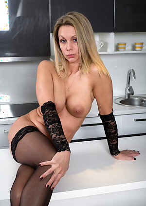 Slutty MILF strips to lacy stockings in the kitchen