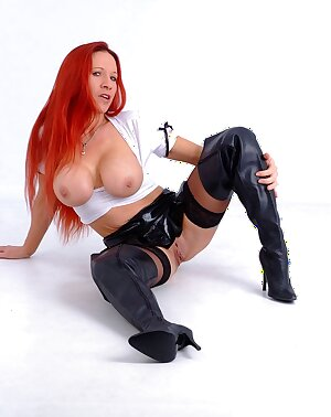 Kinky redhead slut shows off her assets wearing a tiny leather mini skirt and leather thigh boots