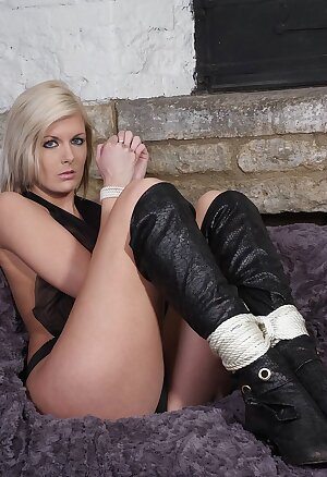 Shy blonde with her hands rope bound to her leather boots