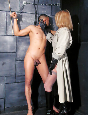 Very hot dominatrix wearing leather gloves and ties up her submissive