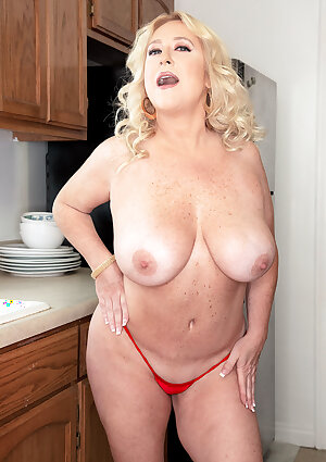 Busty mature housewife Nina Bell undressing in the kitchen