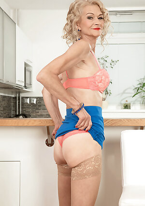 Very skinny granny undressing at kitchen