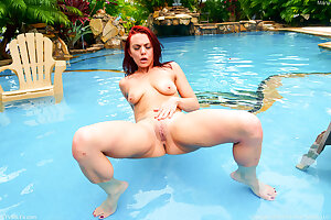 Redhead bitch Maria Jade shows us her shaved pussy by the pool