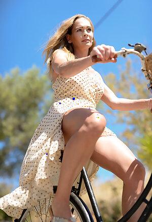 Elegant woman in a polka dot dress riding a bicycle