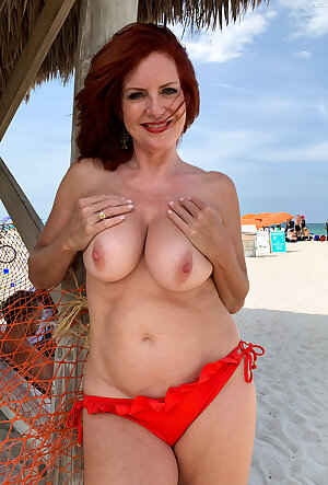 Nude redhead mature female Andi James teases men with big saggy tits on the beach