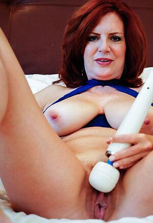 Redhead mature beauty Andi James with hairy pussy masturbates at bedroom