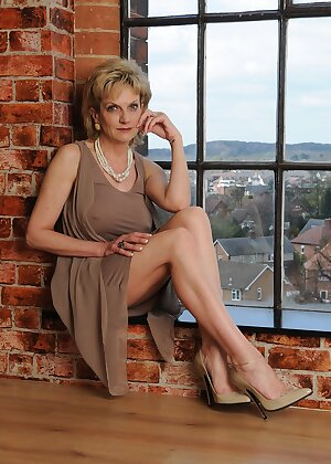 Non nude mature lady shows bare legs in front of window in high heels
