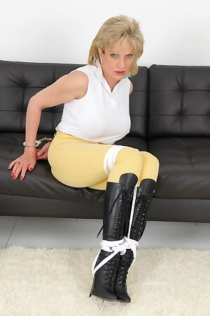 Fully clothed UK mature lady is tied up with rope in black boots