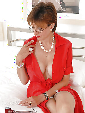 Elegant mature lady in stockings posing on the bed and fingering her pussy