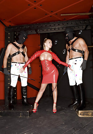Hot mistress in red latex dress Dora Venter has a BDSM groupsex with well-hung guys