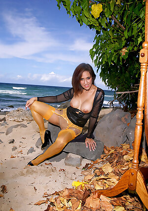 Busty Hawaiian MILF Roni Ford in white stockings and nude pantyhose posing on the beach
