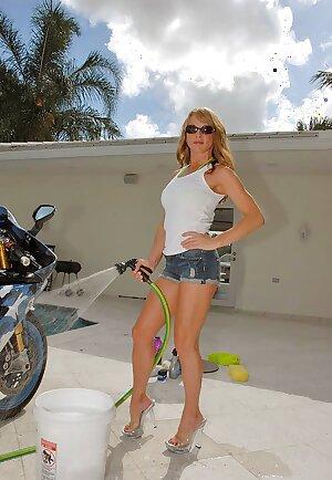 Slutty MILF in revealing bikini washes bike with her sexy tits bare