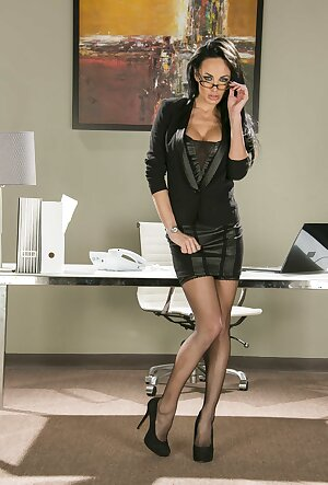 Business woman Alektra Blue teasing with her eyeglasses and stripping in the office